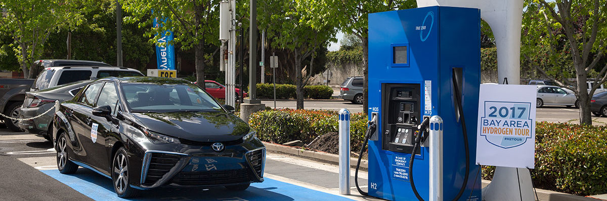 Image of a fuel cell vehicle pulling up to a hydrogen fueling station